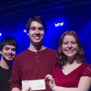 Jérémie Lessard, coordonnateur de l'Association étudiante du Cégep de Matane, remet un chèque de 150 $ au numéro gagnant composé de Émile Prince et de Marie-Dominique Bernard.<br />