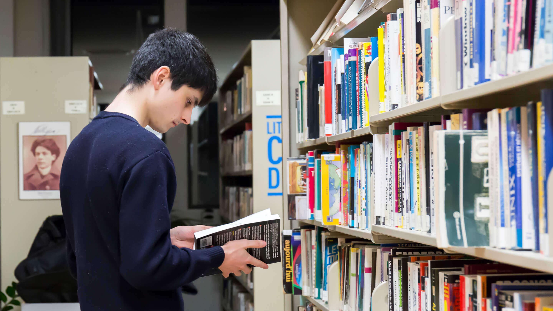 Étudiant qui lit un livre à la bibliothèque