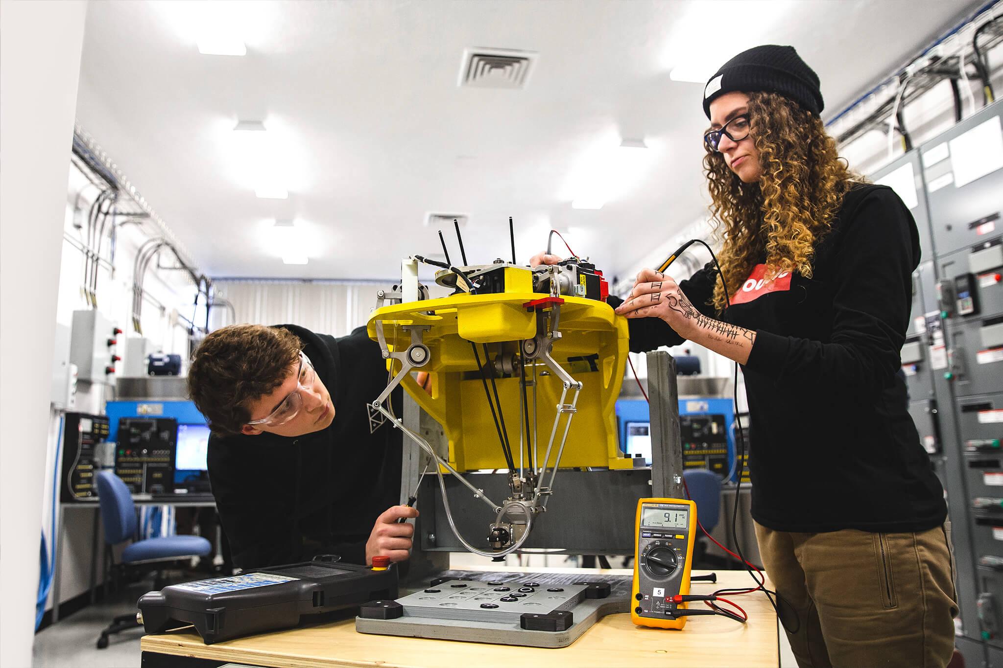 Deux étudiants en électronique travaillant sur un robot