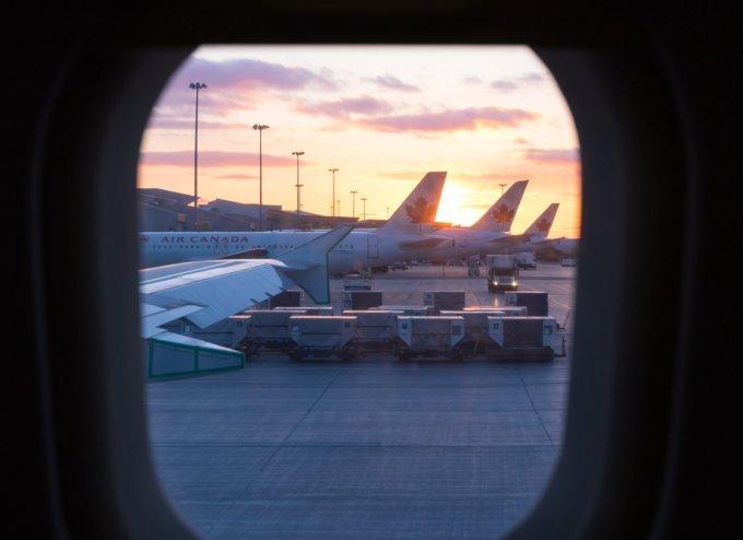 photo à travers un hublot où on voit les avions d'air Canada