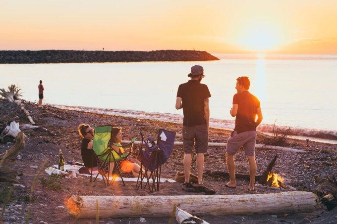 Groupe d'amis qui font un feu sur le bord de la plage