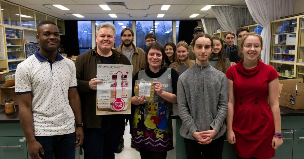 Un groupe d'étudiant en sciences de la Nature, ainsi que leur professeur posant fièrement devant le total de leur campagne de financement.